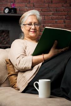 Śliczna starsza indyjska azjatycka dama siedzi na rozkładanym krześle lub sofie, czytając książkę lub używając karty lub laptopa laptop