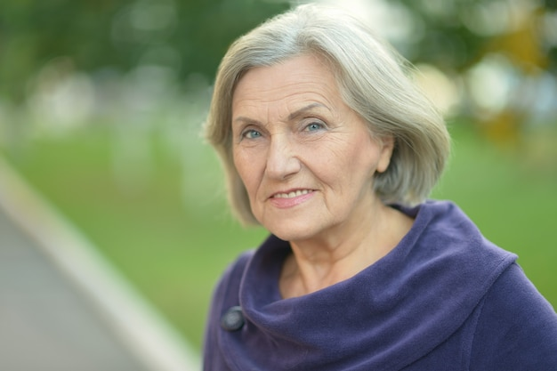 Śliczna starsza kobieta spacerująca po parku