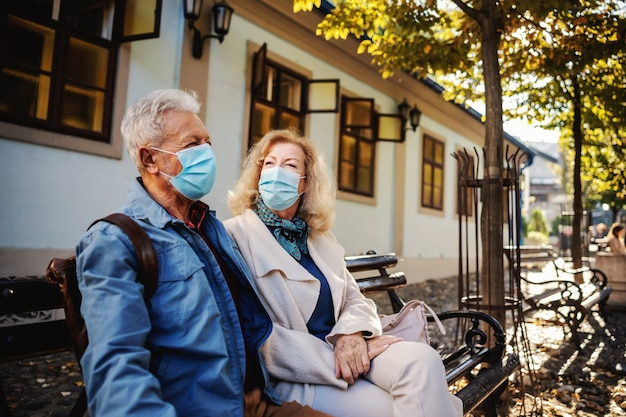 Śliczna starsza para z maskami ochronnymi na siedzeniu na ławce na zewnątrz i rozmowie.