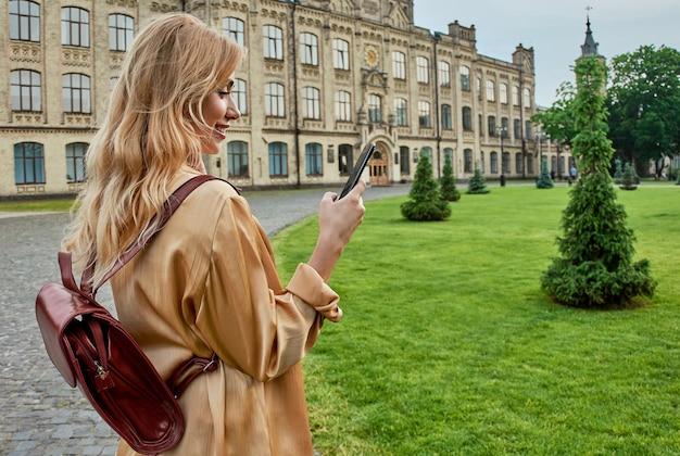 Śliczna studentka korzysta z telefonu komórkowego w pobliżu uniwersytetu. koncepcja technologii.