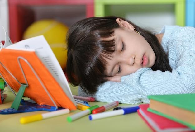 Śliczna studentka śpi w pobliżu książek w klasie