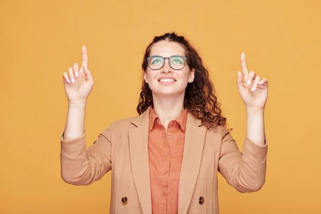 Śliczna studentka z zębatym uśmiechem, wskazująca i patrząca w górę, zwracająca uwagę publiczności na coś bardzo ważnego