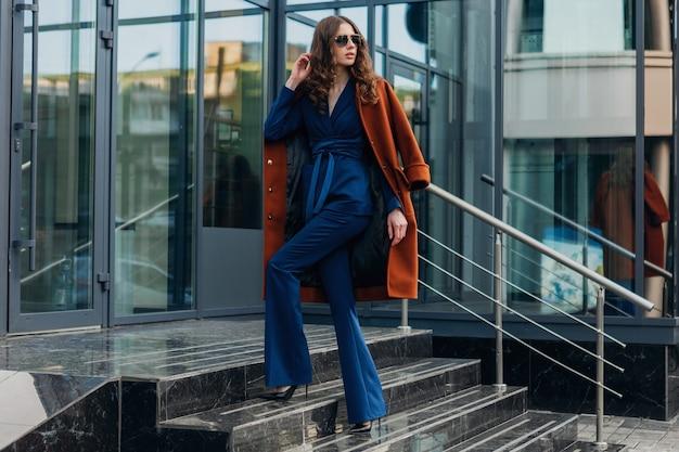 Śliczna stylowa kobieta chodząca po miejskiej ulicy biznesowej ubrana w ciepły brązowy płaszcz i niebieski garnitur, wiosenna jesień modny styl uliczny, w okularach przeciwsłonecznych