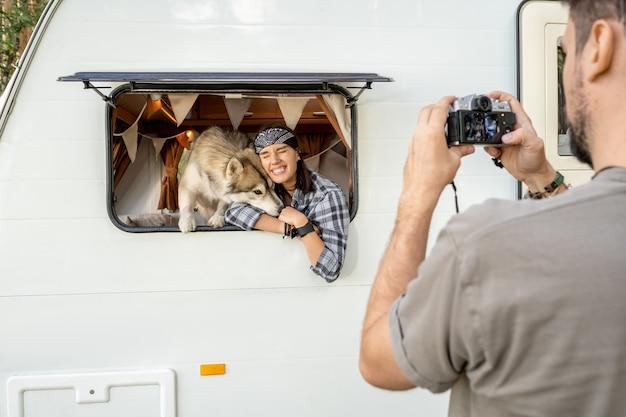 Śliczna suka i czuły pies husky w oknie domu podróży