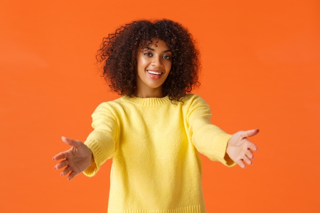 Śliczna sympatyczna, atrakcyjna afroamerykanin z kręconymi włosami, wyciągająca ręce do przodu, gotowa do przytulania, obejmująca przyjaciela i uśmiechnięta radośnie, gratulująca.