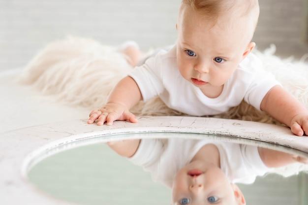Śliczna szczęśliwa 7-miesięczna dziewczynka w pieluchy leżącej i grającej
