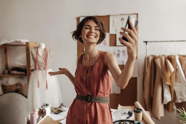 Śliczna szczęśliwa atrakcyjna krótkowłosa kobieta w lnianej czerwonej sukience szeroko się uśmiecha, pozuje w przytulnym biurze projektanta mody i robi selfie