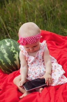 Śliczna szczęśliwa blondynka o niebieskich oczach dziewczyna 8 miesięcy w trawie z arbuzem i telefonem