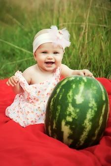 Śliczna szczęśliwa blondynka o niebieskich oczach dziewczyna 8 miesięcy w trawie z arbuzem