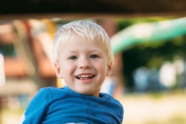 Śliczna szczęśliwa chłopiec z blondynem ma zabawę na boisku w pogodnym letnim dniu.
