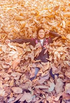 Śliczna szczęśliwa dziewczyna kłaść w jesieni suchy liść.
