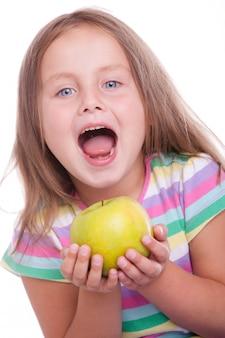 Śliczna szczęśliwa dziewczyna z zielonym jabłkiem