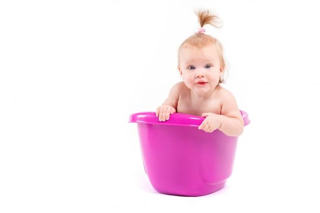 Śliczna szczęśliwa dziewczynka bierze skąpanie w balii