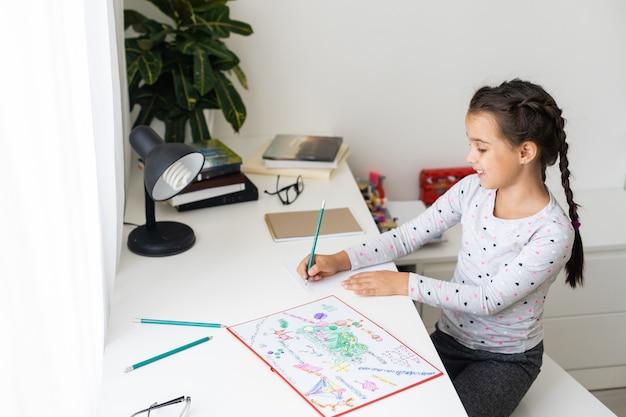 Śliczna szczęśliwa mała dziewczynka pisze coś w swoim zeszycie