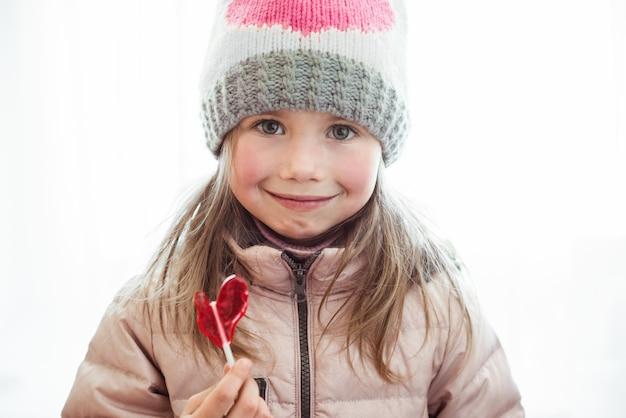 Śliczna szczęśliwa mała dziewczynka z lollipop candy z copyspace