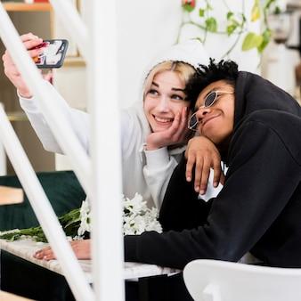 Śliczna szczęśliwa międzyrasowa nastoletnia młoda para bierze selfie na telefonie komórkowym