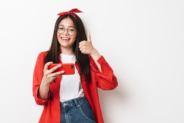 Śliczna szczęśliwa nastolatka w stroju casual stojąca na białym tle nad białą ścianą, trzymająca telefon komórkowy, kciuk w górę