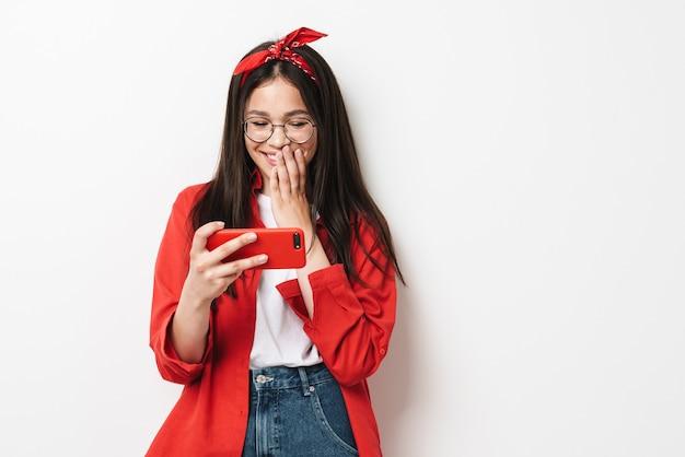 Śliczna szczęśliwa nastolatka w stroju casual stojąca na białym tle nad białą ścianą, trzymająca telefon komórkowy