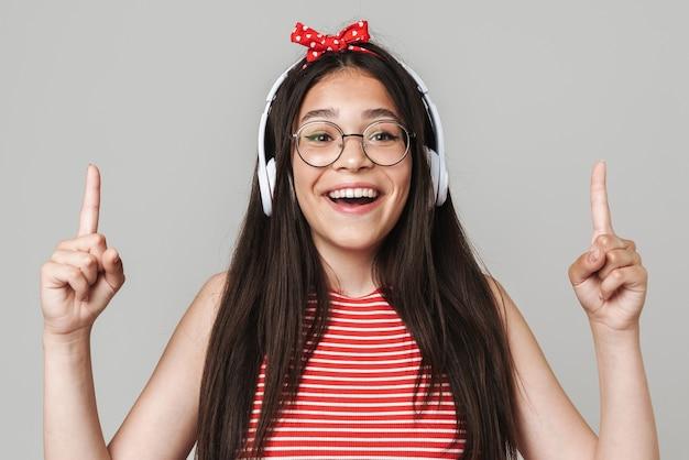 Śliczna szczęśliwa nastolatka w swobodnym stroju, stojąca na białym tle nad szarą ścianą, słuchająca muzyki przez słuchawki, wskazująca w górę