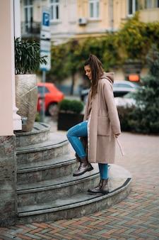 Śliczna szczęśliwa uśmiechnięta brunetka spacerująca po mieście