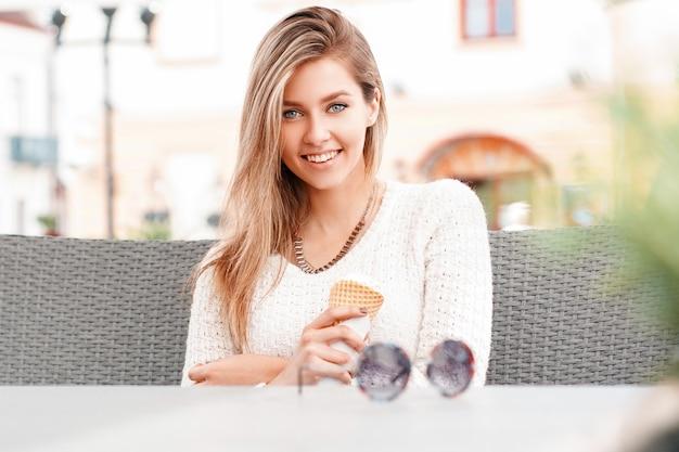 Śliczna szczęśliwa wesoła młoda kobieta w pięknym uśmiechu o niebieskich oczach o blond włosach w sweter z dzianiny siedzi i uśmiecha się w kawiarni na świeżym powietrzu. stylowa dziewczyna jedzenie lodów.