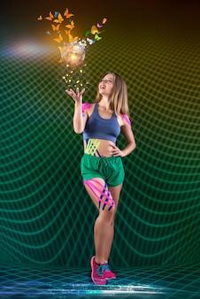 Śliczna szczupła młoda dziewczyna sportowca przed zieloną siatką rzuca piłkę i motyle. pojęcie magii sportu i wiary w zwycięstwo