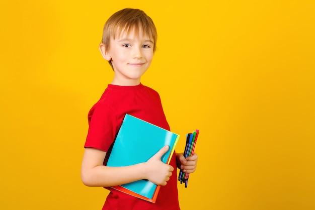 Śliczna szkolna chłopiec z notatnikami na żółtym tle. powrót do szkoły.