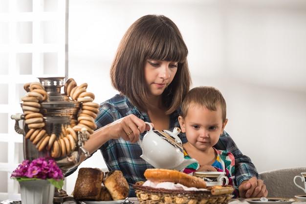 Śliczna troskliwa matka nalewa herbatę małemu ślicznemu synowi
