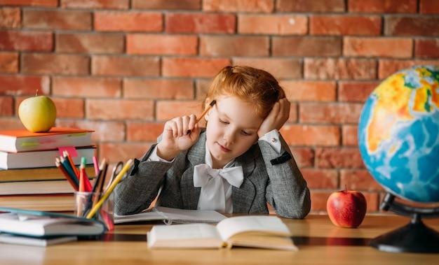 Śliczna uczennica odrabia lekcje przy stole z podręcznikami, jabłkami i kulą ziemską.