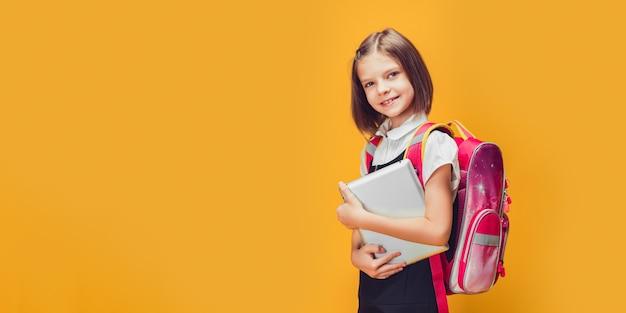 Śliczna uczennica przygotowuje się do pójścia do szkoły z plecakiem i tabletem z powrotem do koncepcji szkoły