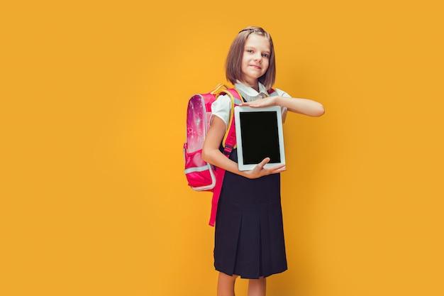 Śliczna uczennica przygotowuje się do pójścia do szkoły z plecakiem pokazującym tablet z powrotem do koncepcji szkoły