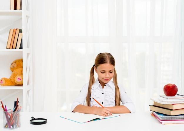 Śliczna uczennica robi pracie domowej