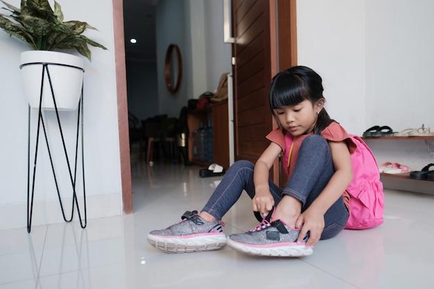 Śliczna uczennica szkoły podstawowej założyła buty