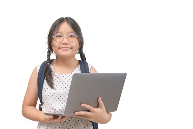 Śliczna uczennica trzyma laptopa na białym tle, powrót do koncepcji szkoły i edukacji