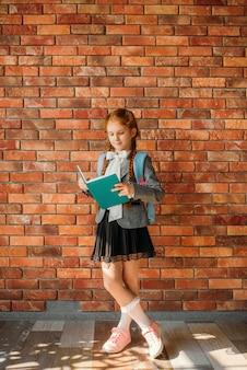 Śliczna uczennica z tornistrem czyta podręcznik