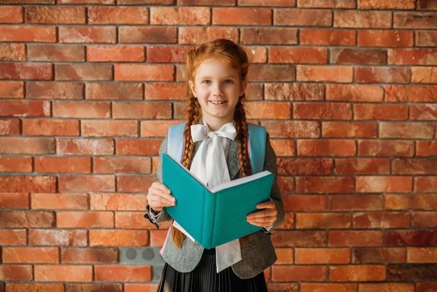 Śliczna uczennica z tornistrem trzyma podręczniki