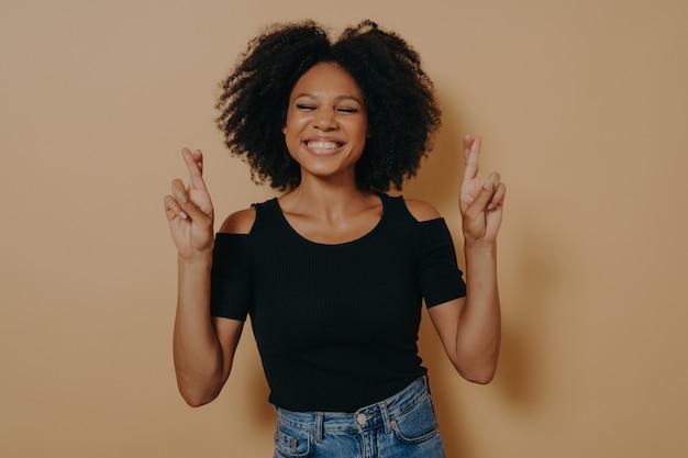 Śliczna urocza afroamerykanka pozuje w zwykłych ubraniach, gestykulując palcami skrzyżowanymi znakami, uśmiechając się z nadzieją i zamkniętymi oczami. koncepcja szczęścia, przesądów i mowy ciała