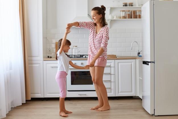 Śliczna urocza dziewczynka tańcząca z matką, r czująca niesamowity taniec z kochającą mamusią, wyrażająca szczęście i pozytywne emocje, rodzinną zabawę w domu.