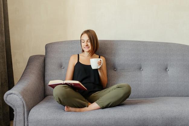 Śliczna urocza uśmiechnięta dziewczyna czyta książkę i pije herbaty podczas gdy relaksujący na kanapie w domu. styl życia hobby.