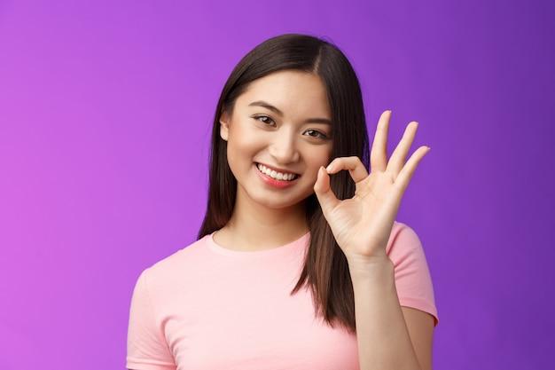 Śliczna uśmiechnięta azjatka zatwierdza dobry plan, pokazuje znak w porządku ok, przechyla głowę uroczo się uśmiecha, jest zadowolona z doskonałej jakości produktu, daje pozytywne opinie, akceptuje wybór, stoi na fioletowym tle.