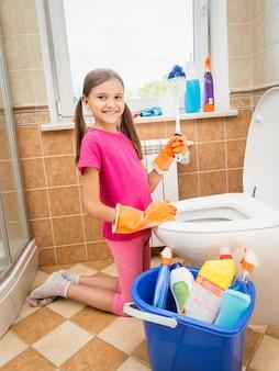 Śliczna uśmiechnięta dziewczyna czyści toaletę za pomocą pędzla