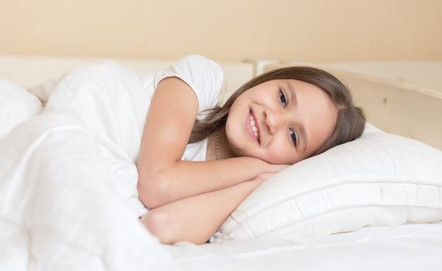 Śliczna uśmiechnięta dziewczyna leżąca na poduszce i patrząca na kamerę