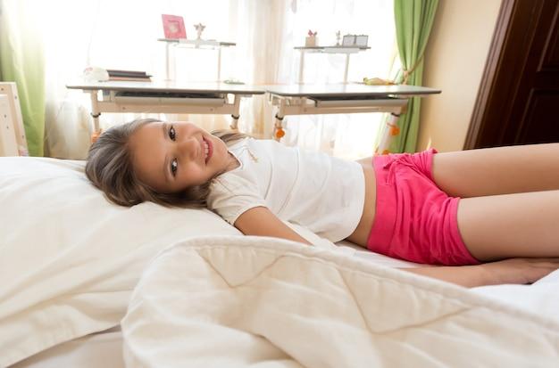 Śliczna uśmiechnięta dziewczyna leżąca w łóżku w słoneczny poranek