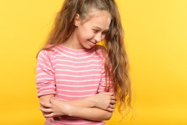 Śliczna, uśmiechnięta dziewczyna nieśmiała. portret zawstydzonego dziecka na żółto. koncepcja emocji i wyrazu twarzy.