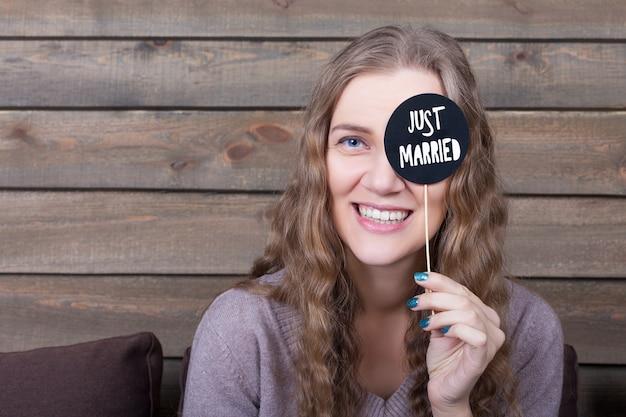 Śliczna uśmiechnięta dziewczyna pokazuje zabawną ikonę na patyku z napisem właśnie żonaty