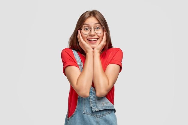 Śliczna uśmiechnięta dziewczyna trzyma obie dłonie na policzkach, uśmiecha się szeroko, będąc w dobrym nastroju po spacerze z chłopakiem