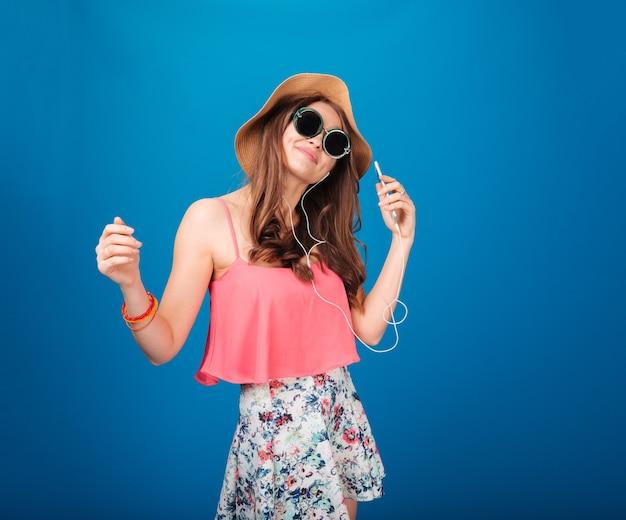 Śliczna uśmiechnięta dziewczyna w kapeluszu i okularach przeciwsłonecznych słucha muzyki na niebieskim tle