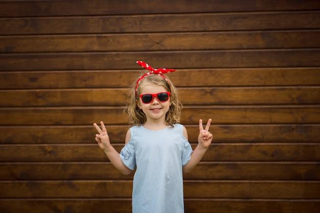 Śliczna uśmiechnięta dziewczyna w okularach przeciwsłonecznych robi znakowi v.