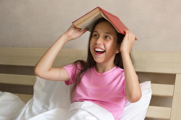 Śliczna uśmiechnięta dziewczyna z długimi ciemnymi włosami siedzi w łóżku w ciągu dnia trzyma dach książki nad głową