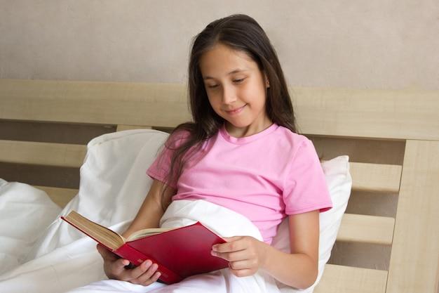 Śliczna uśmiechnięta dziewczyna z długimi włosami w różowej koszulce siedzi w łóżku i czyta książkę w ciągu dnia